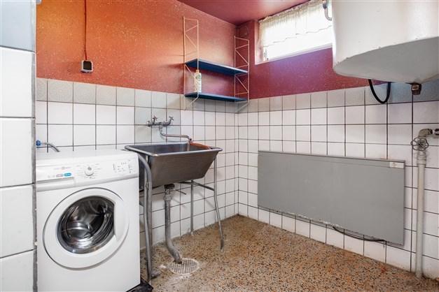 Tvättstuga med nyare tvättmaskin och stor varmvattenberedare. Ett torkrum finns intill.