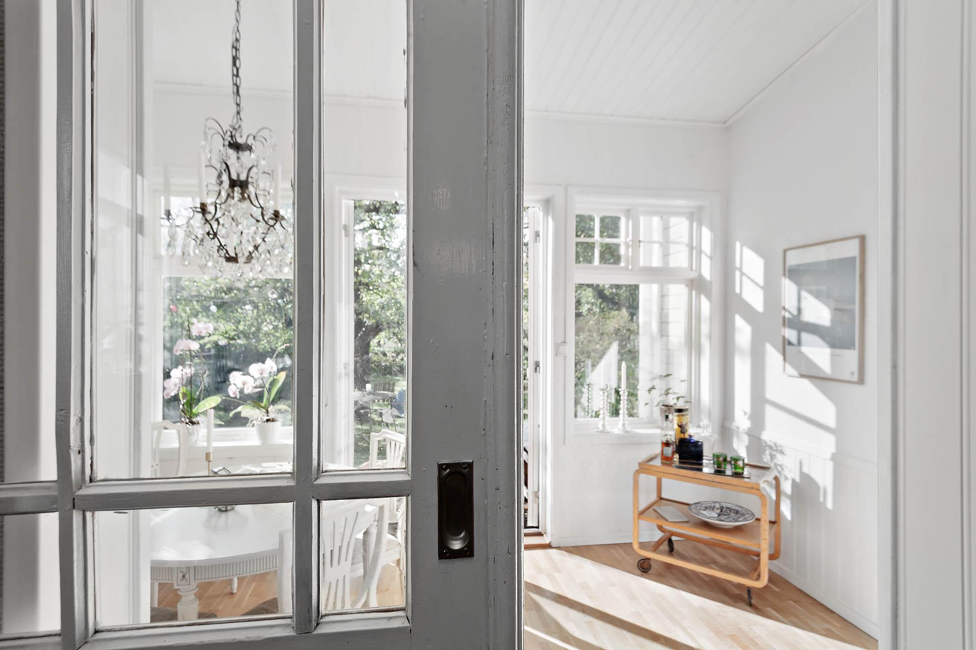 Vackra skjutdörrar gränsar av mellan vardagsrum och blomsterrum.