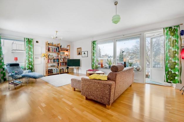 Vardagsrummet är ljust och rymligt med fönster i tre väderstreck