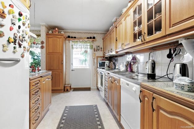 Kök med gott om förvaring och arbetsutrymme med utgång till inglasad altan