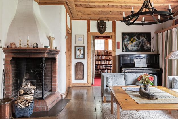 Vardagsrummet med den pampiga öppna spisen och mot röda rummet