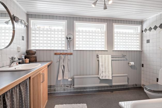 Välplanerat badrum med en fondvägg i trä som gör det mer ombonat.