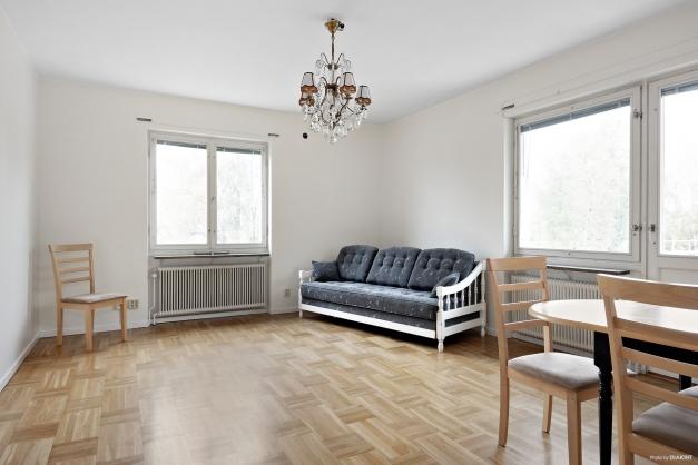 Rymligt vardagsrum med fint parkettgolv och ljusinsläpp från två håll.