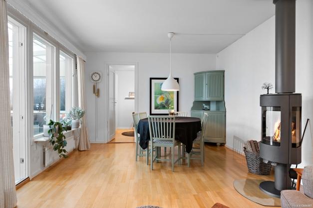 Vardagsrum med braskamin och plats för såväl sittgrupp som matsalsbord. Utgång till inglasat uterum & altan.