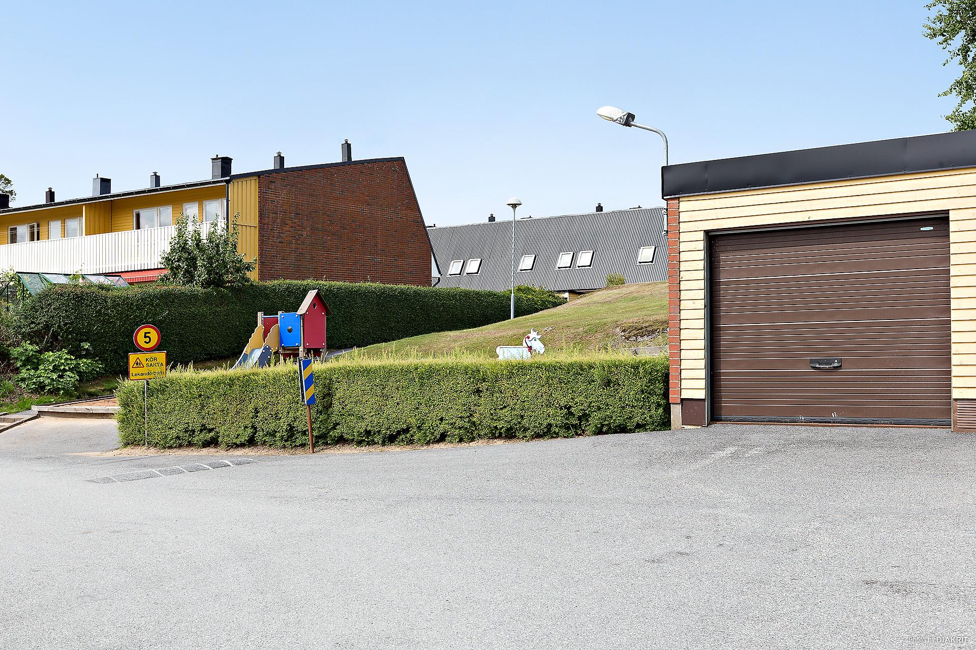 Garaget i bild tillhör bostaden. I bakgrunden ser ni radhuset samt en lekplats.