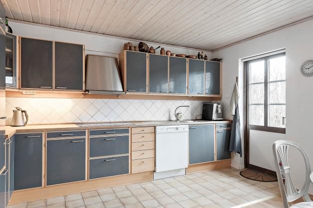 Snyggt kök med tåligt klinkergolv och utgång till uteplatsen.