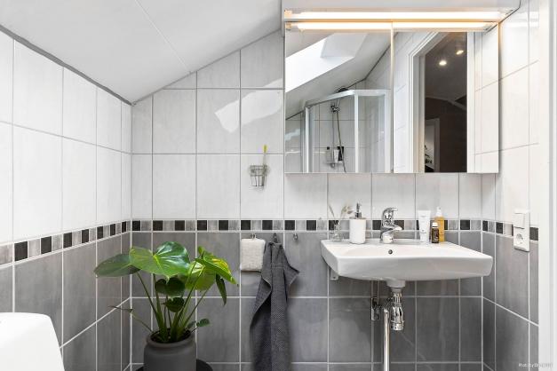Helkaklat badrum på övre plan inrett med dusch, handfat med spegel samt toalett.