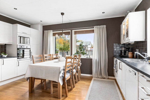 Modernt kök med mycket förvaring och en trevlig matplats vid fönsterpartiet.
