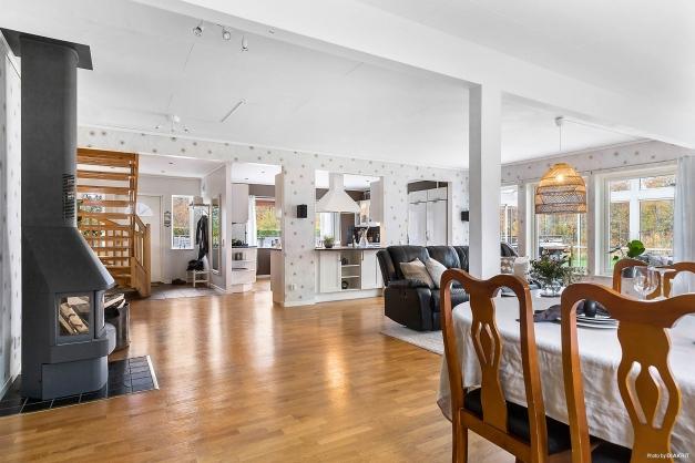 Stort och socialt vardagsrum inrett med en mysig braskamin som ger god värme i hela huset.