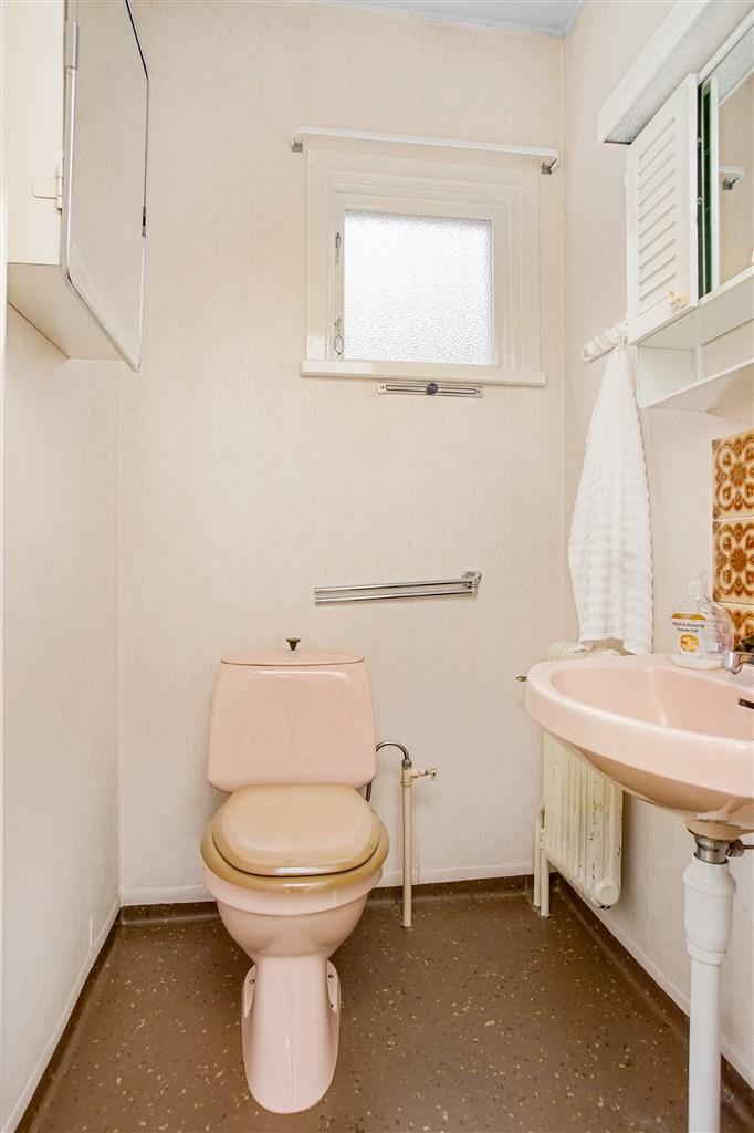 Wc utrustad med wc och handfat i rosa porslin och fönster.