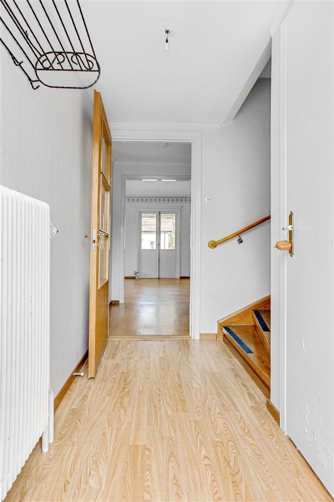 Hall med uppgång till övervåningen och nergång till källaren.