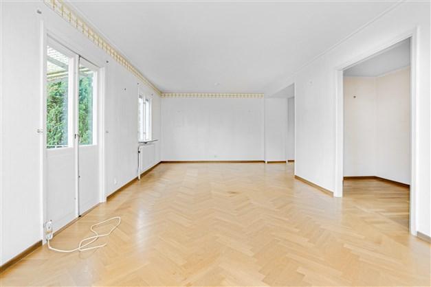 Stort vardagsrum i vinkel med fin stavparkett på golv.