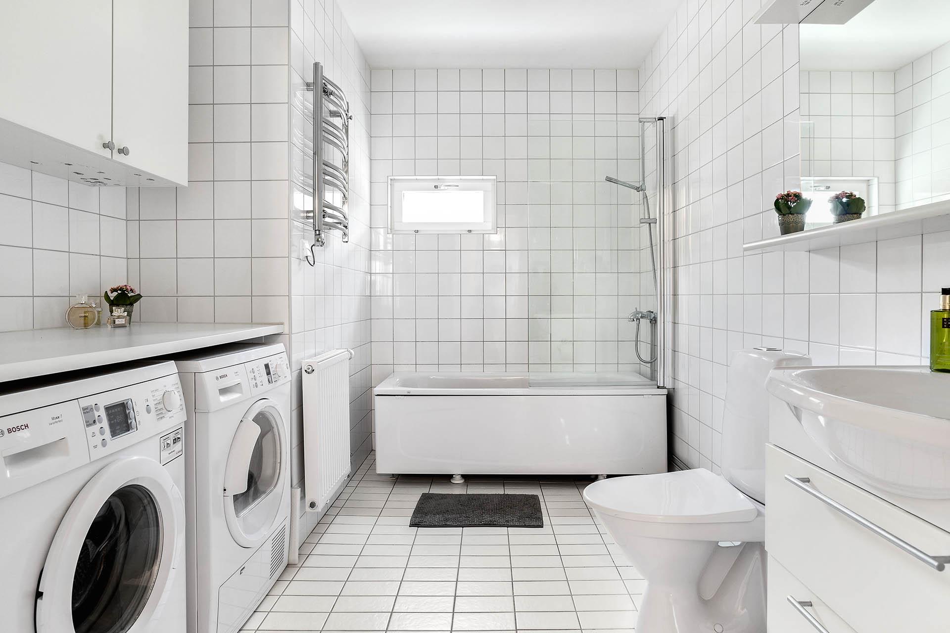 Badrum med tvättmaskin och troktumlare