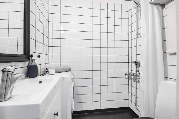 Badrum med kaklade väggar och våtrumsmatta på golv.