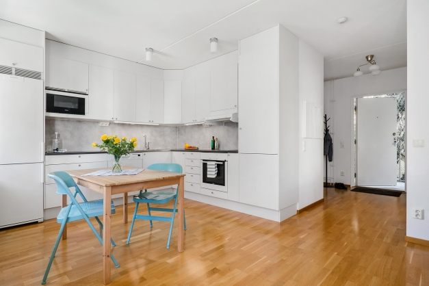 Modernt kök i vitt med vy mot hall