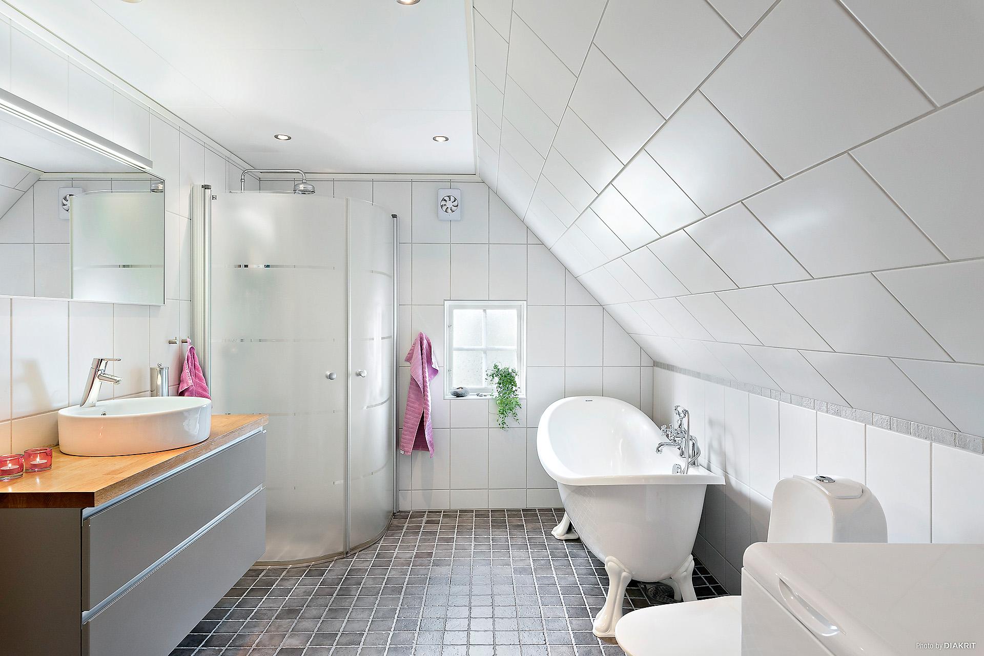 Rymligt, helkaklat badrum med badkar med lejontassar, duschhörna, kommod, toalett och tvättmaskin.