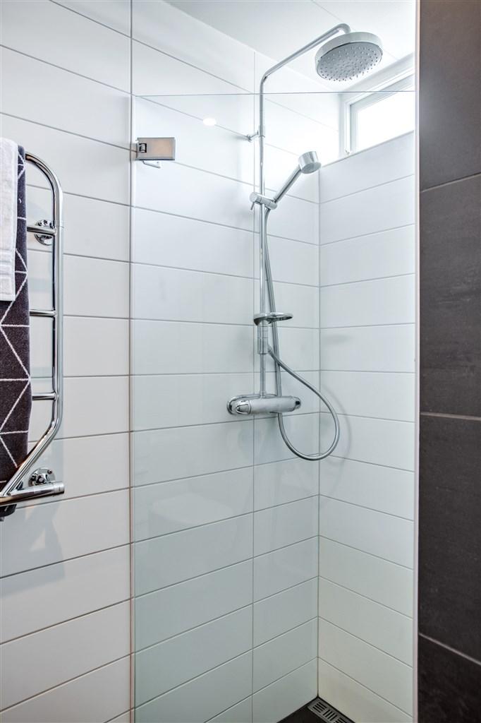 Till höger om hallen finns dusch och wc som är stilrent och smakfullt renoverat 2006. Klinker med skön golvvärme och kakel på väggarna.