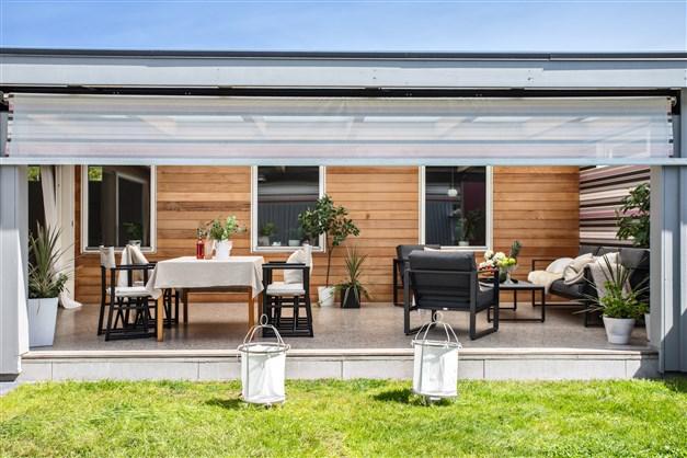 Uteplats som är delvis under tak med slipad betongyta i samma nivå som innergolvet. Husets fasad mot innergården är klädd med vacker cederträpanel.