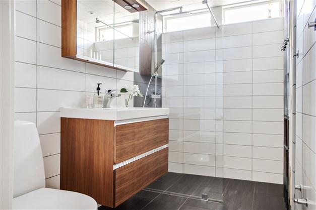 Smakfullt och stilrent renoverat badrum 2013. Helkaklade ljusa väggar med dusch, på golvet ligger klinker med skön golvvärme.  Inredning från Ballingslöv, wc från Ifö och tvättställ. Handdukstorken håller era handdukar torra oavsett årstid.