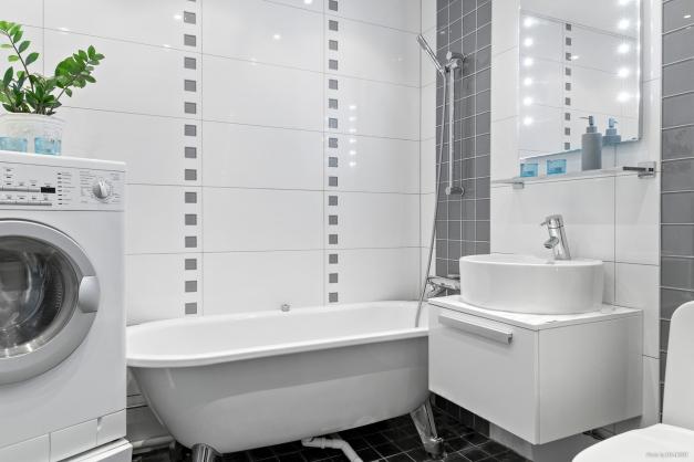 Helkaklat badrum med badkar och en upphöjd kombinerad tvättmaskin/torktumlare.