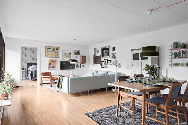 Stort härligt vardagsrum med fflera fönster och vy mot innergården