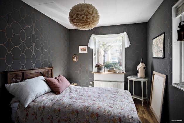 Ljust sovrum på entréplan med två fönster och en praktiskt garderob.