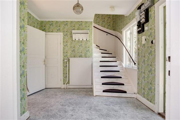 Hall med uppgång till övervåningen och nedgång till källaren.