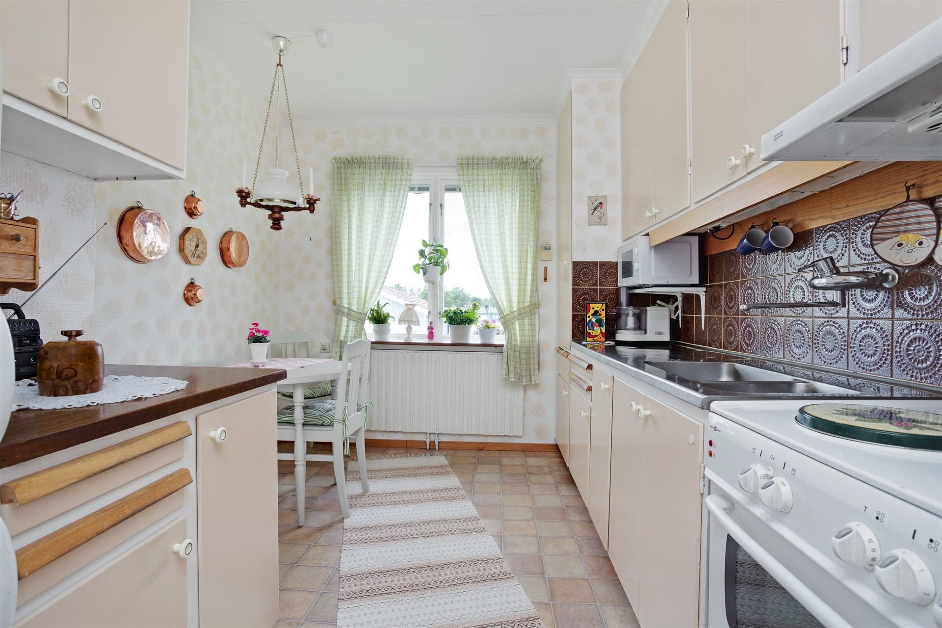 Ljust kök med bra arbetsytor och förvaring.