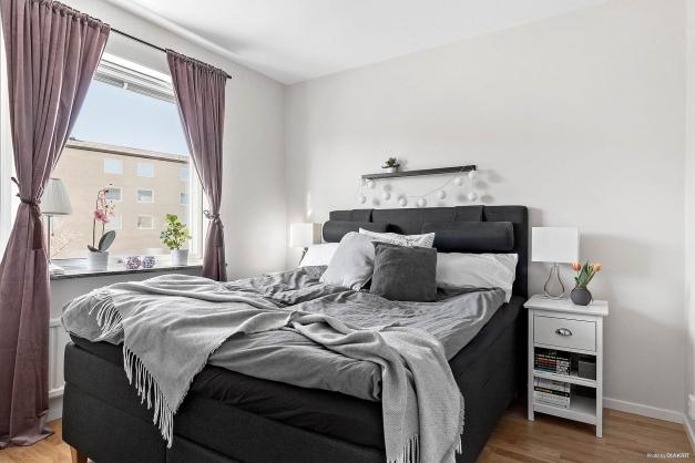 Ljust och mysigt sovrum med plats för dubbelsäng och nattduksbord.