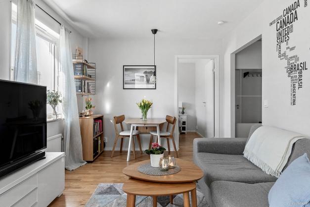 Ljust och rymligt vardagsrum med plats för soffgrupp och matbord.
