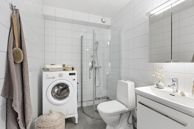Stort och ljust duschrum med kombinerad tvättmaskin/torktumlare.