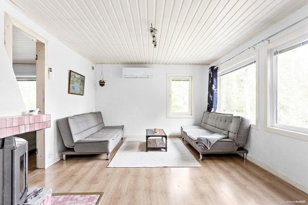 Vardagsrum med stora fönsterpartier och öppen spis
