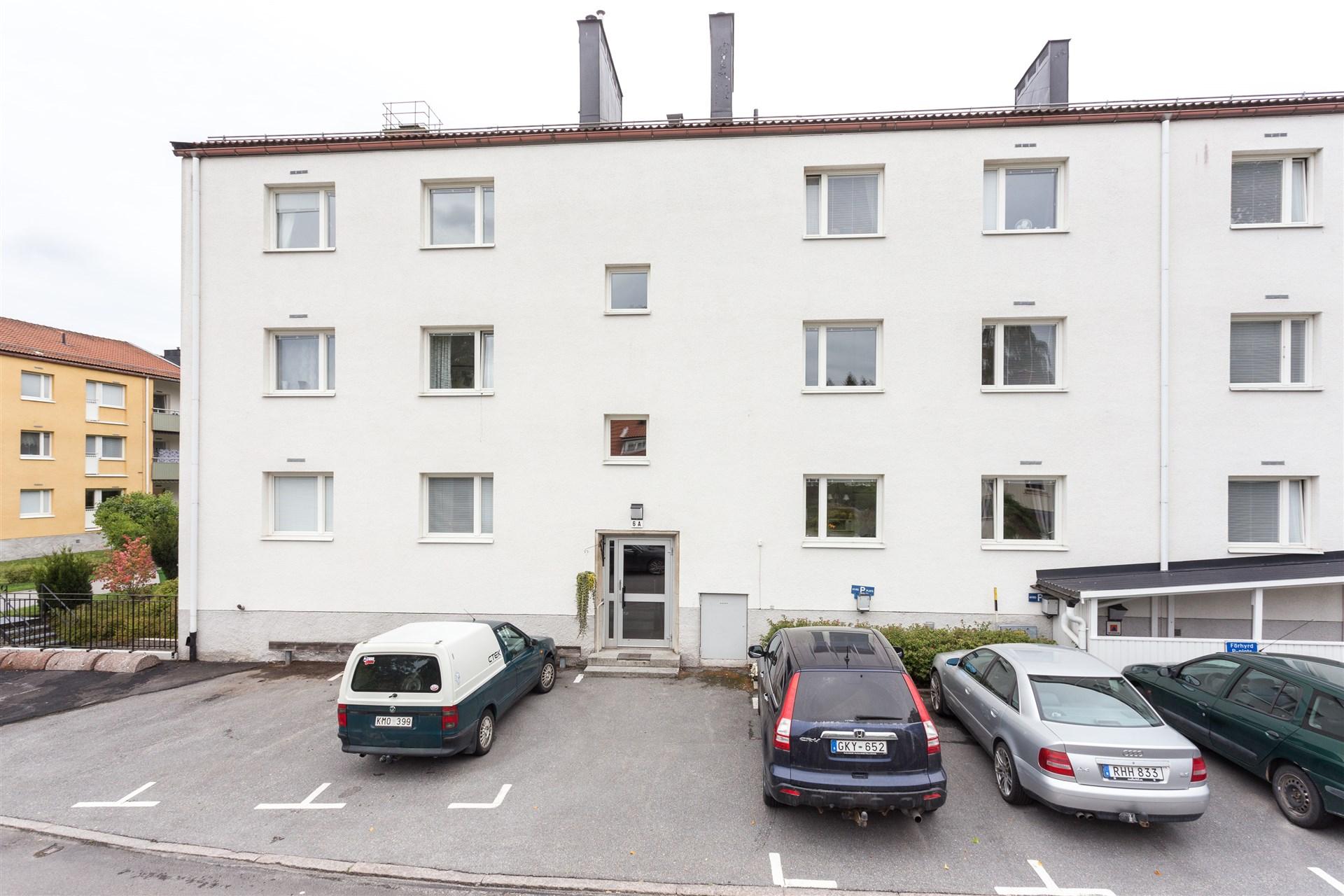 Framsidan på huset med parkeringsplatser.