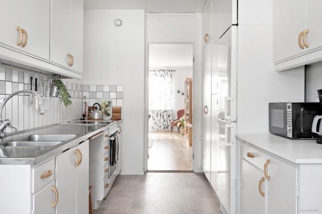 Ljust kök med rymliga utrymmen och goda förvaringsmöjligheter.