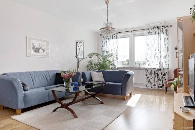 Ljust vardagsrum med stora utrymmen för både soffgrupp samt matsalsmöbel.