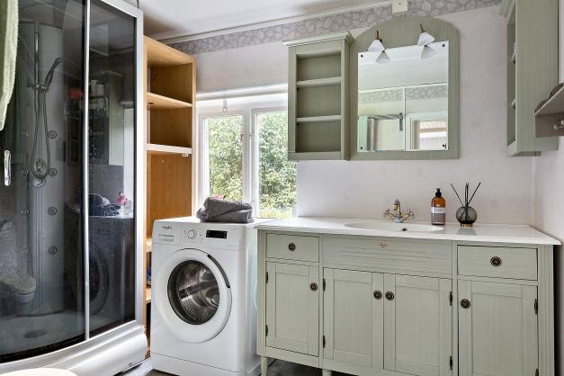 Badrum med duschkabin och tvättmaskin