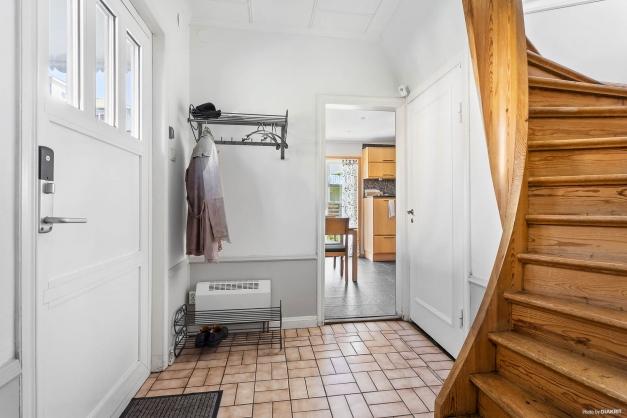 Inbjudande hall i anslutning till kök. Härifrån nås källarplan och trappa som leder till övre plan