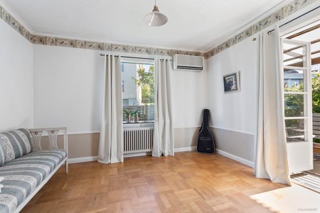 Sovrum 1 med elegant ekparkett på golv och bröstning på väggar. Utgång till altan i söderläge