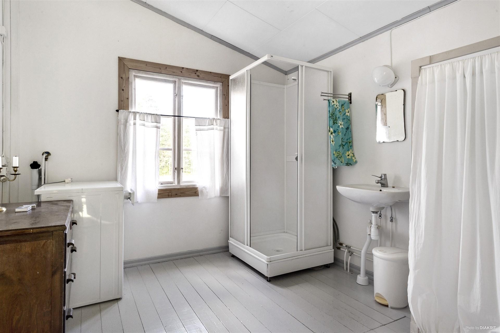 Duschrum med duschkabin, tvättställ och tvättmasin