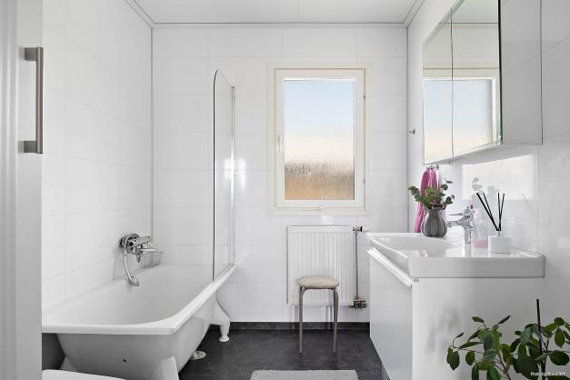 Badrum med våtrumsmatta på golvet och våtrumspanel på väggarna. Utrustat med badkar, wc, handfat med kommod samt linneskåp.