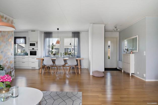 Öppen planlösning mellan kök, vardagsrum och hall.