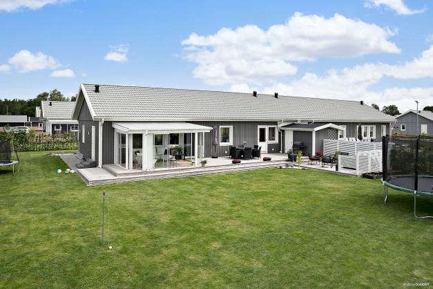 Vy över baksidan av bostaden. Stor gräsmatta vilket bjuder in till spring och lek.