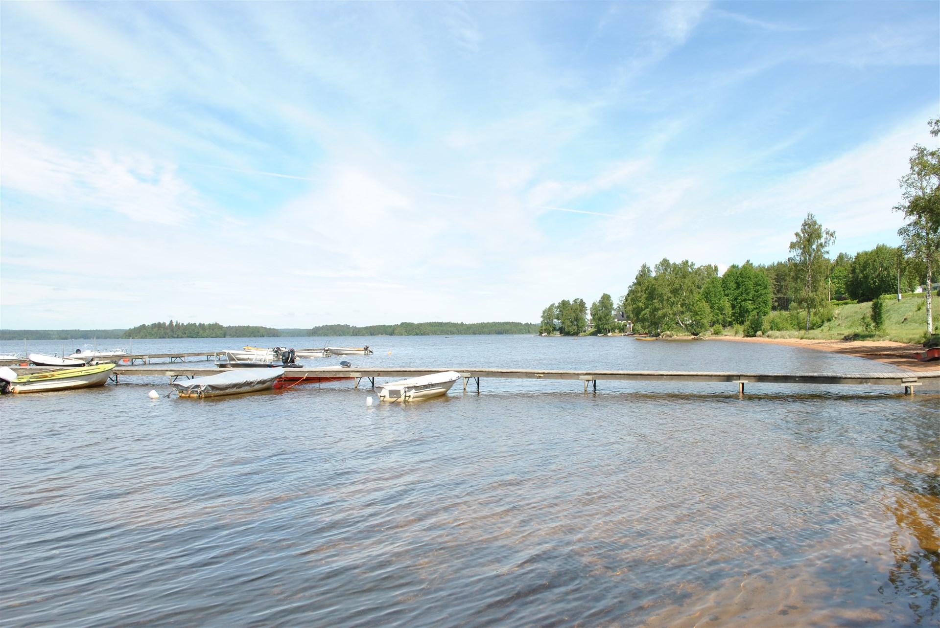Badplats med sandstrand och båtplats