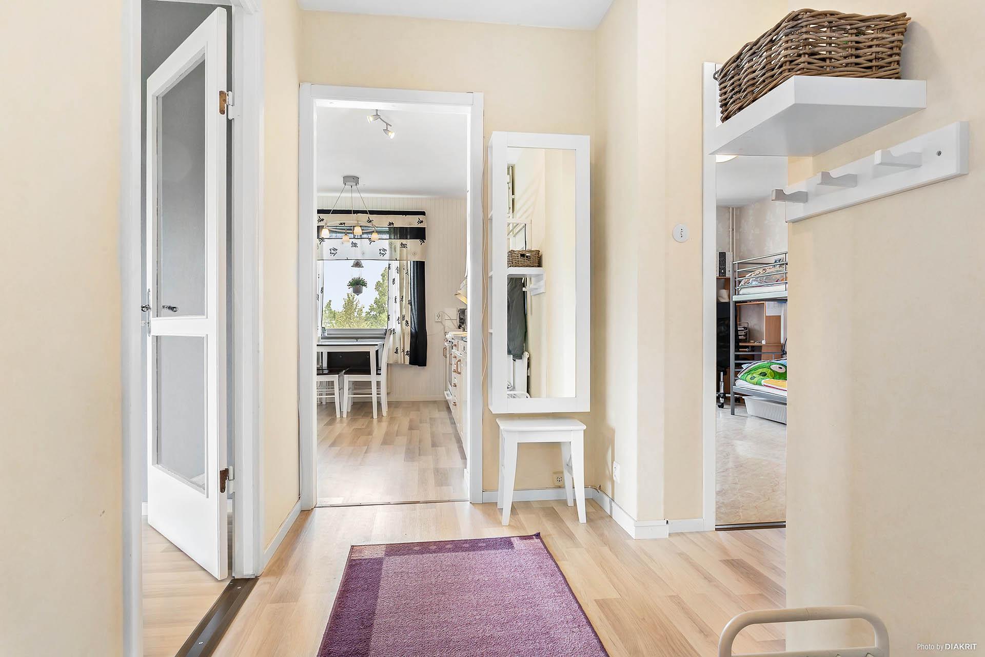 Hall med öppning mot vardagsrum, kök samt sovrum.