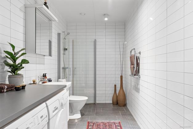Modernt och välplanerat badrum inrett med både tvättmaskin och torktumlare samt en praktisk arbetsbänk.
