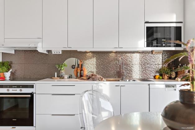 Köket präglas av vita luckor, en vit och stilfull bänkskiva, kakel i en metallic färgad ton som skiftar färg beroende på ljus.