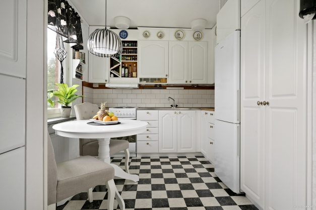 Ljust trevligt kök med plats för matbord vid fönster.