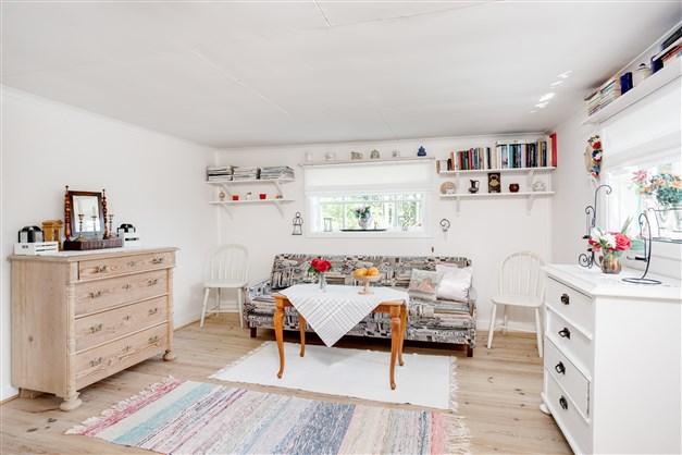 Vardagsrum med två högre fönster som ger fint ljus och gör rummet lättmöblerat.