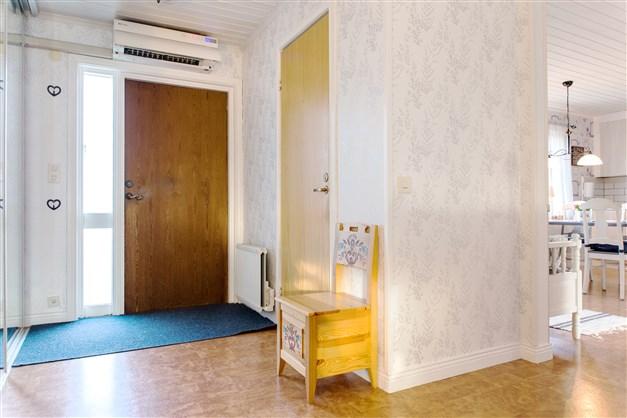 Hall med stor garderob och dörr till toalett