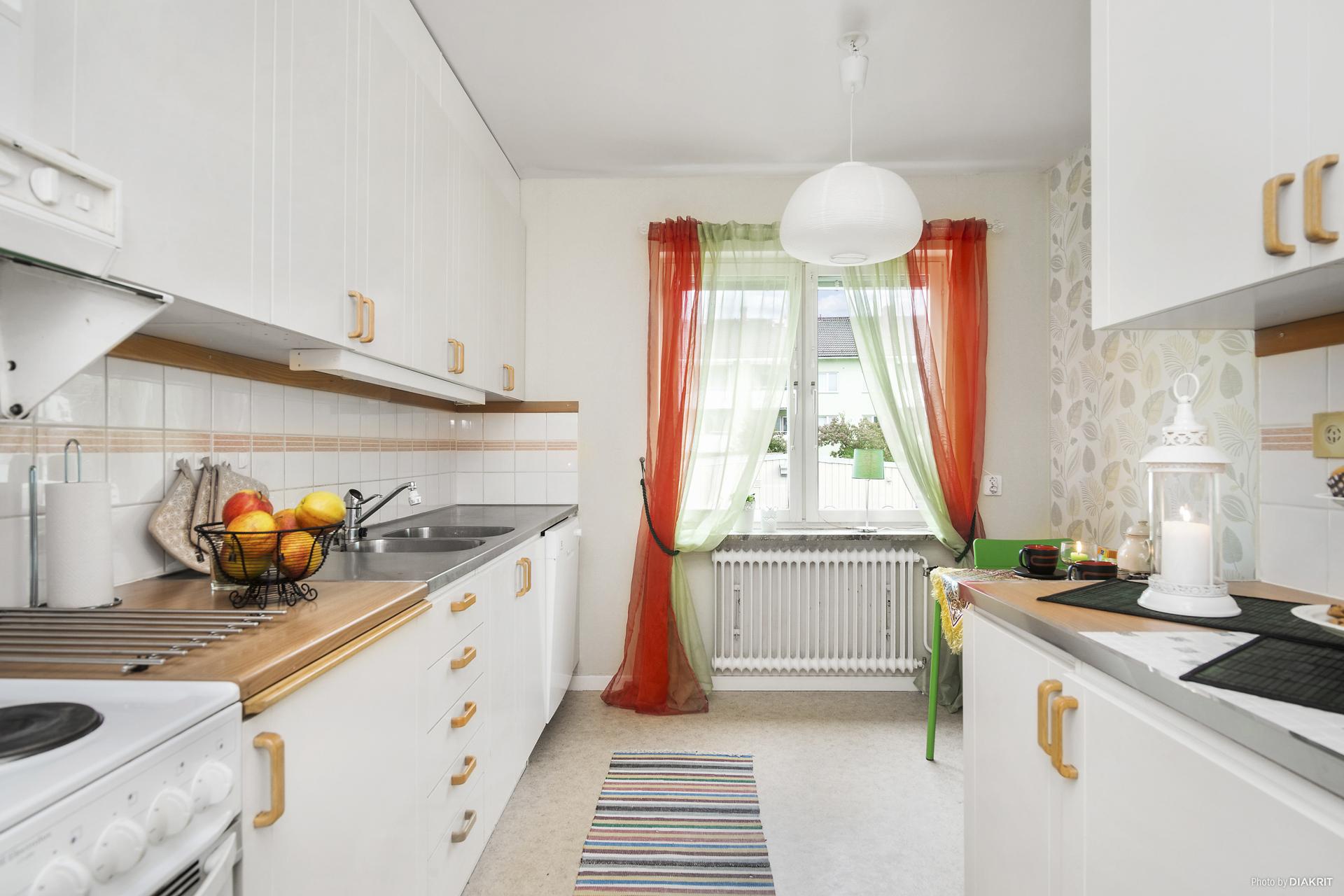 Ljust kök med fondvägg och plastmatta på golv.